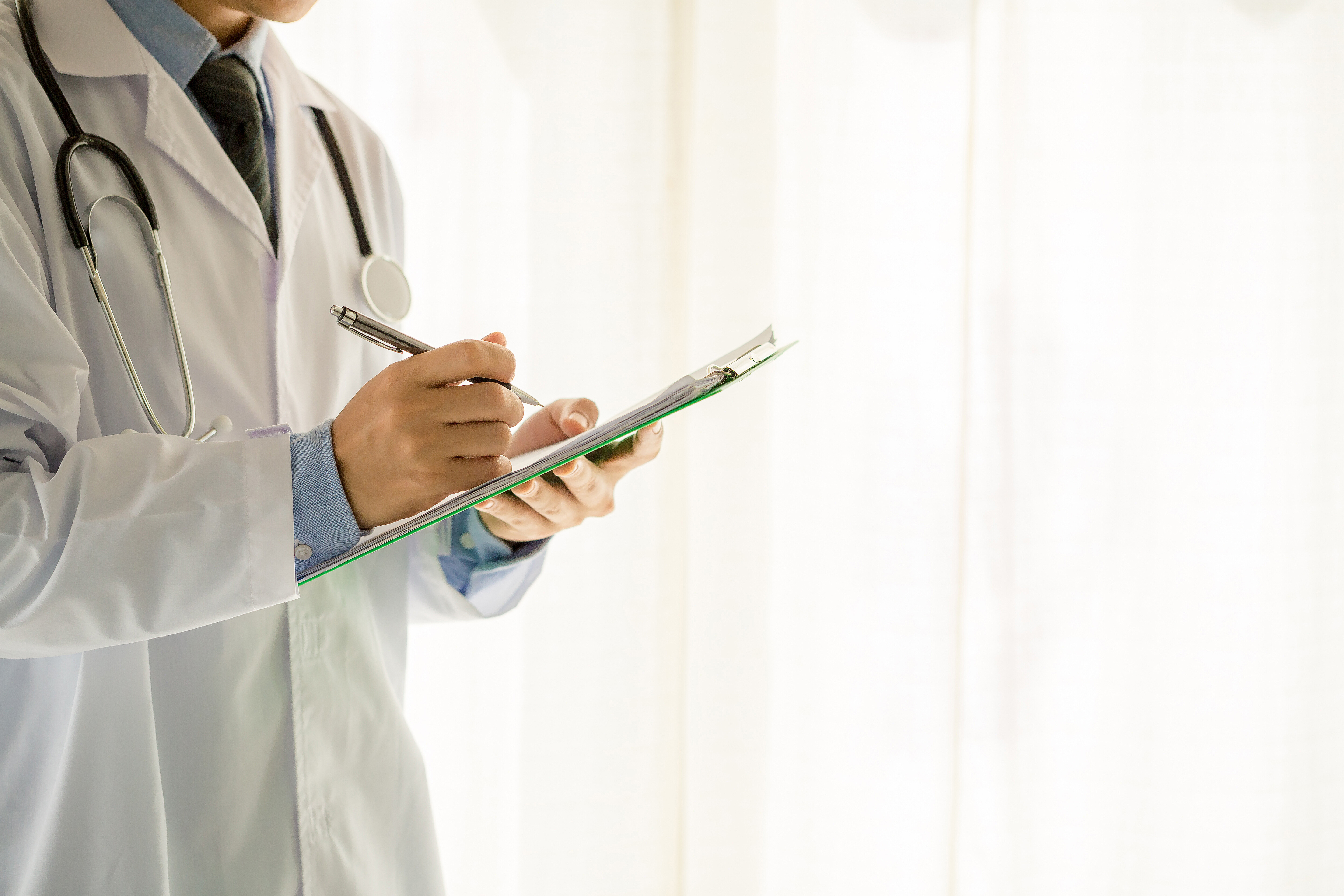 medical physician writing on a clipboard